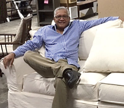 Ali Hosein strikes a pose on a couch, briefly relaxing from his role as vice president of international freight and merchandising for Rooms To Go.