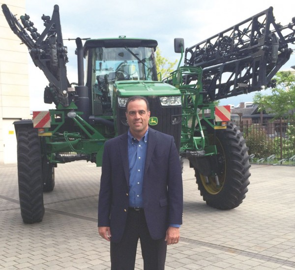 David A. Panjwani, Deere & Co.'s director of worldwide logistics, poses with a big green unit of heavy equipment outside the company's factory in Mannheim, Germany.