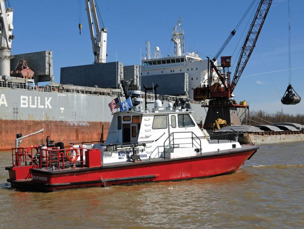 Behind a security patrol and fire boat, transloading activity takes place at the Port of South Louisiana, the Western Hemisphere's No. 1 tonnage port