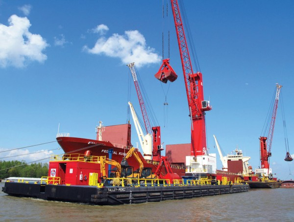 At St. Bernard Port, downriver from New Orleans, barge-mounted floating cranes are used in the transfer of cargo between oceangoing ships and river barges.
