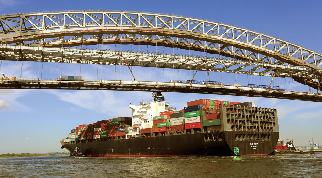China Ocean Shipping Co.'s 6,000-TEU E.R. India passes under the Bayonne Bridge as crews work above to raise the roadbed to accommodate passage of larger container vessels.