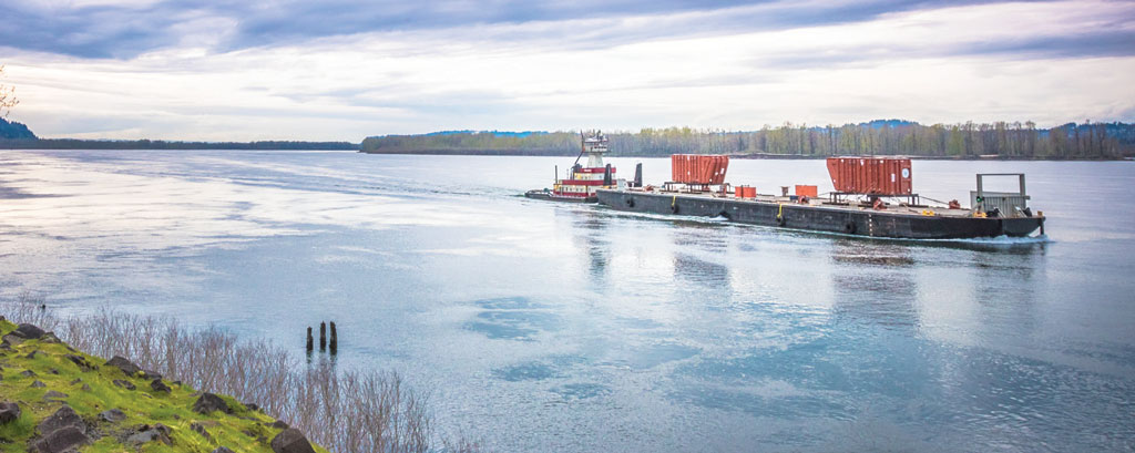 Hydroelectric transformers being transported via river barge along the Columbia River