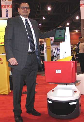 Adrian Kumar, vice president of solutions design for North America for DHL Supply Chain, sidles up to a LocusBot at the Retail Industry Leaders Association's gathering in Phoenix. (Photo by Paul Scott Abbott, AJOT)