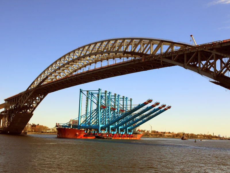 Indicative of multibillion-dollar infrastructure investment by the private sector at the Port of New York and New Jersey, four new super-post-Panamax cranes pass under the raised Bayonne Bridge roadbed on their way to the APM Terminals Elizabeth facility in New Jersey.