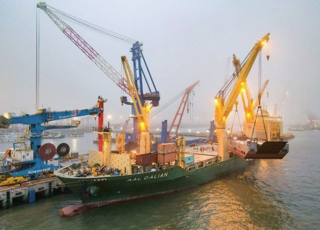 The MPP, AAL Dalian, lifts a barge onto its deck.