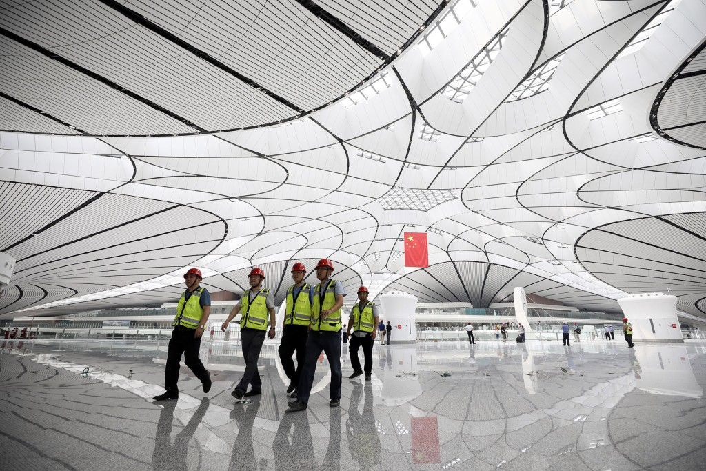 Workers walk through the terminal building. Photographer: STR/AFP via Getty Images