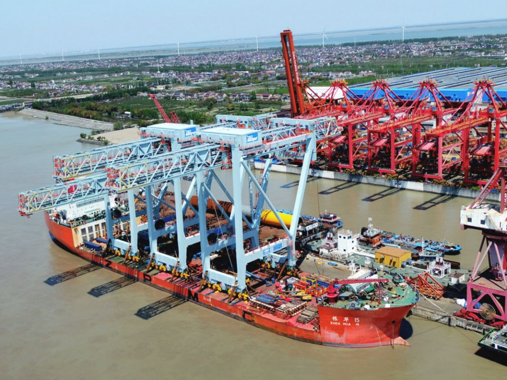 Three new neo-Panamax cranes, capable of efficiently working megacontainerships, are loaded for transport to the Port of Boston at the manufacturing facility of Shanghai Zhenhua Heavy Industries Co. Ltd., or ZPMC, the world leader in fabrication of such units.