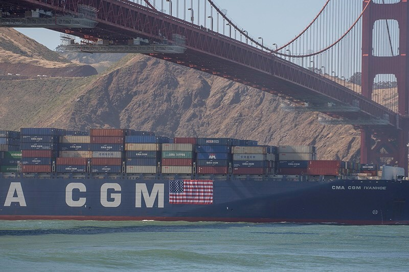 The CMA CGM Ivanhoe displays the U.S.A. Flag as it navigates under the Golden Gate Bridge on Independence Day