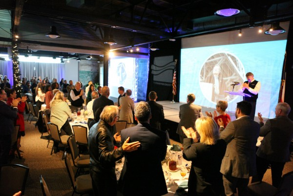 Event attendees stand in honor of John LaRue at Thursday's annual State of the Port.