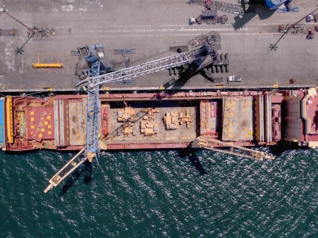 Bird's-eye view of mining trucks being loaded under deck