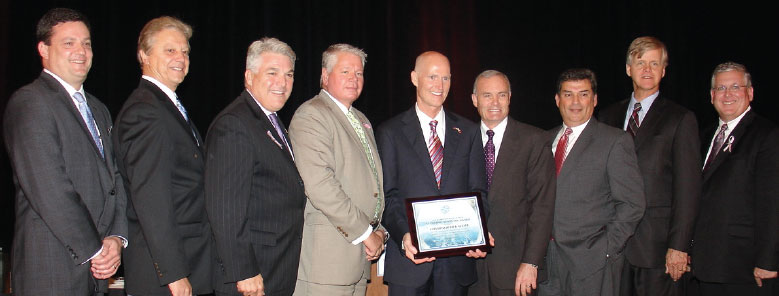 FL Governor, Rick Scott, center, is flanked by (L to R)) Doug Wheeler – president & CEO of the Florida Ports Council, Val Schwec – Port of Fernandina, Paul Anderson – Port of Tampa, Bill Johnson – PortMiami, Brian Taylor – Jacksonville Port Authority, Manny Almira – Port of Palm Beach, Steve Cernak – Port Everglades, John Walsh – Port Canaveral (Photo by Paul Scott Abbott, AJOT)