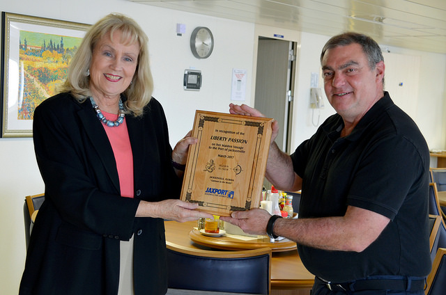 Victoria Robas, JAXPORT's Blount Island Terminal Director, presents Liberty Passion Captain James Meyers with a commemorative plaque onboard the ship.