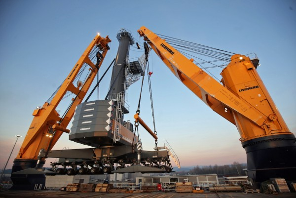 Two Liebherr heavy lift ship cranes, type CBB 4700-450, are unloading a Liebherr mobile harbour crane, type LHM 550, in the Port of Monfalcone, Italy.