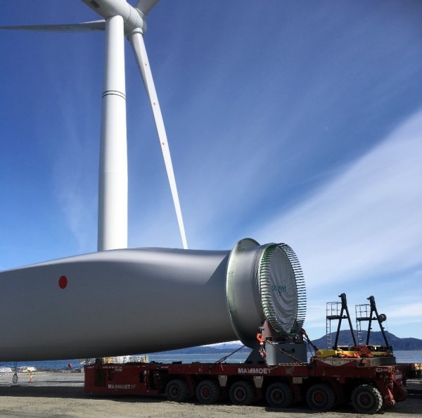Transporting a blade. One of the completed turbines in the background.
